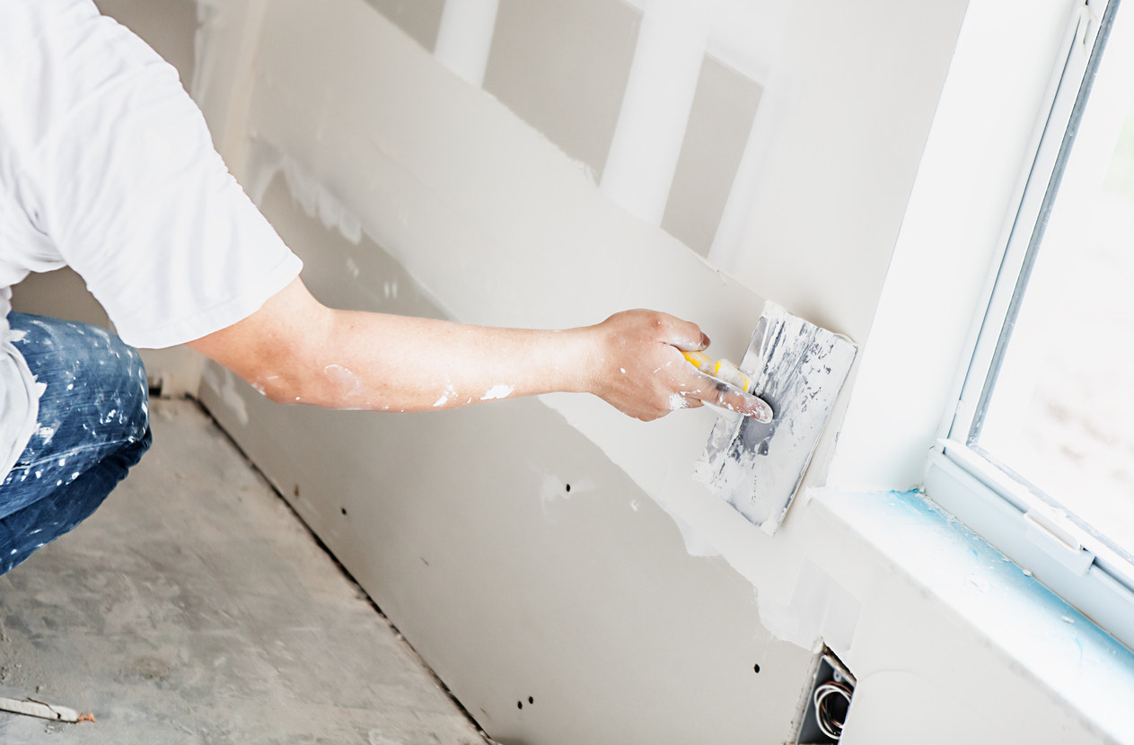 Plasterboard with attapulgite additive being installed by construction worker