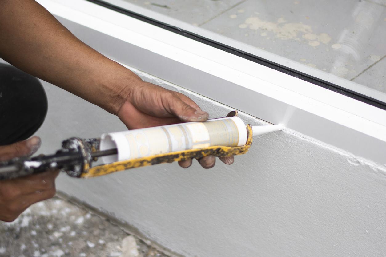 Repairman hand installing the windows with gun silicone. closeup